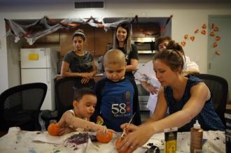 Art therapist Emily Sharp helps children paint pumpkins at a Halloween-themed art group at Lantern's Jasper Hall