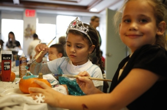 Two children paint pumpkins during a special Halloween event at Lantern's Jasper Hall in the Bronx