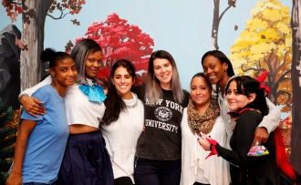 Seven Lantern staff and young adults pose in front of a mural at a Halloween event in the Bronx