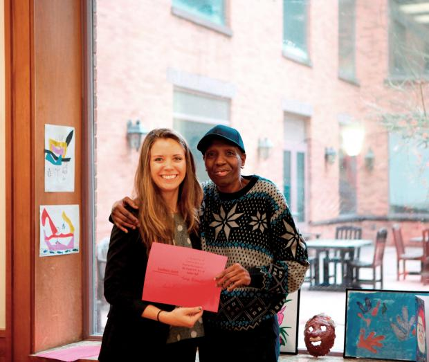 Art Therapist Emily Sharp poses poses with a resident and their artwork at Amber Hall, during the annual Lantern art show