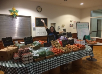 Health and Wellness Coordinator Kristina Rodriguez stands in front of Lantern's Clover Hall Fresh Food Box display