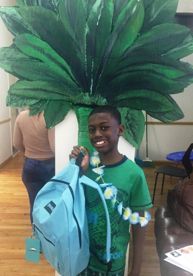 A child who lives at Lantern's Cedars Hall proudly shows his donated backpack, in front of a palm tree made by another Lantern resident