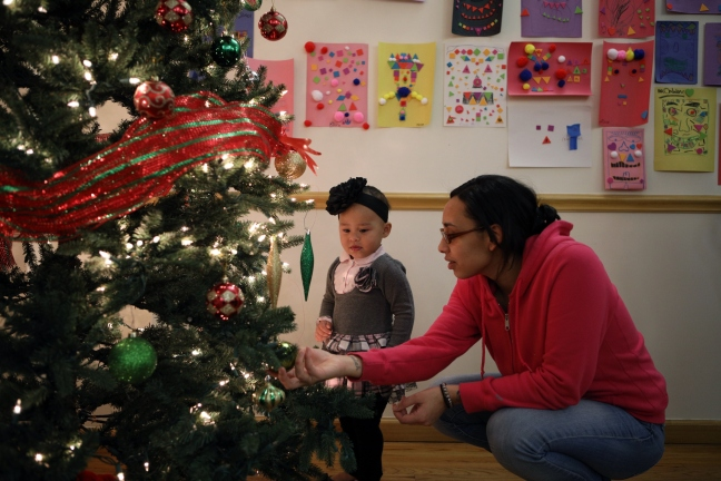 A mother shows her child the Christmas tree decorations at Lantern Community Services