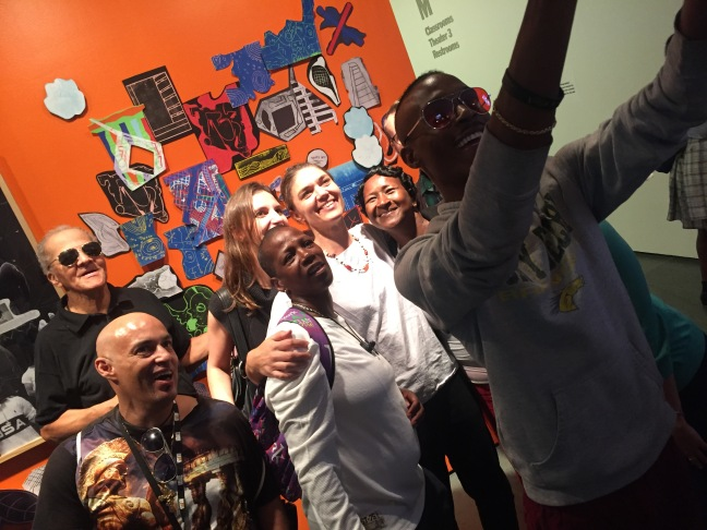 Lantern Community Services residents and staff take a selfie in front of their work 'Block Party', on display at MoMA