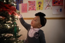 A Lantern child enjoys the tree at their holiday celebration