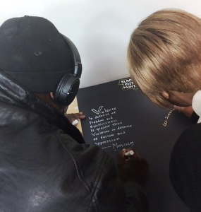 Residents write on a Black History Month poster at Rustin House